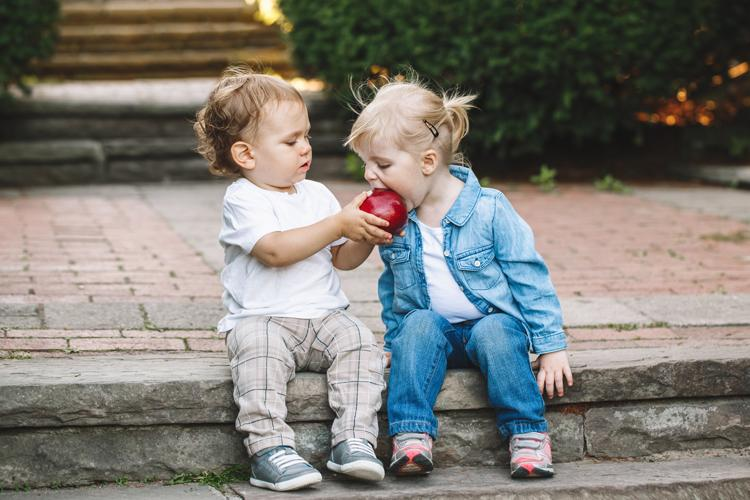 Photo of two children sharing an apple.